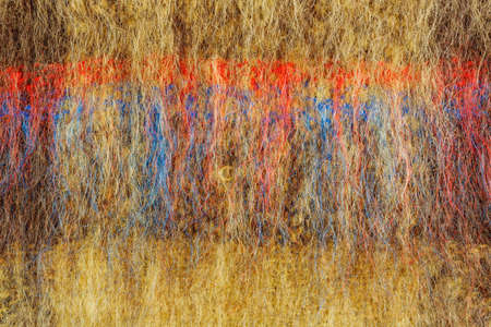 Abstract texture of brown knitted wool with black red and blue stripes. Background of natural wool