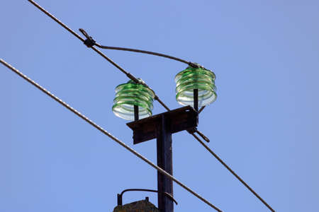 Glass insulators of a transmission line supports close-up on blue sky background Stock Photo