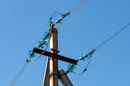 Concrete pillar of a power transmission line with wires close-up against a blue sky Stock Photo