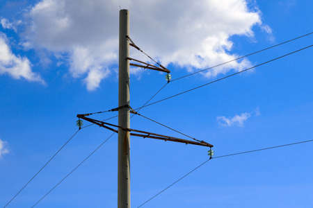 Concrete pole of power line on blue sky background with clouds Stock Photo