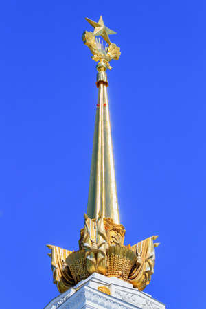 Moscow, Russia - August 01, 2018: Gilded spire with soviet star closeup on the tower of pavilion Central on Exhibition of Achievements of National Economy (VDNH) in Moscow on a blue sky background Éditoriale