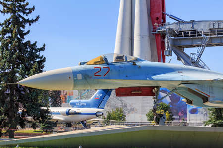 Moscow, Russia - August 01, 2018: Russian fighter SU-27 on a background of Vostok booster rocket against blue sky closeup on Exhibition of Achievements of National Economy (VDNH) in Moscow