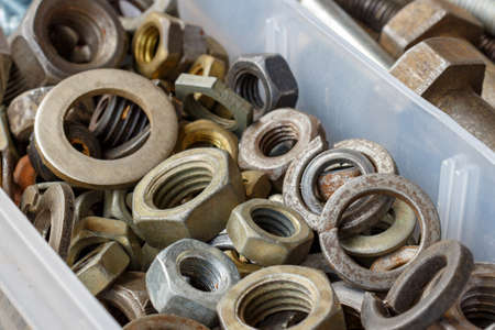 Used nuts and washers in storage box closeup