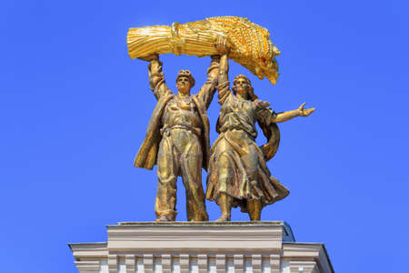 Moscow, Russia - August 01, 2018: Gilded figures of Tractor driver and collective farm girl closeup on top of arch of Main entrance on VDNH in Moscow against blue sky