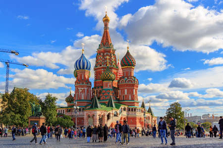 Moscow, Russia - September 30, 2018: Tourists walking on Red Square in Moscow against St. Basil Cathedral in sunny day