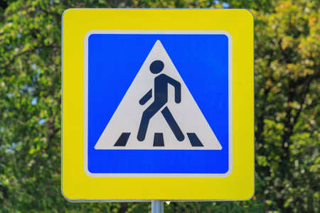 Road sign of Pedestrian crossing against green tree closeup at sunny summer day Stock Photo