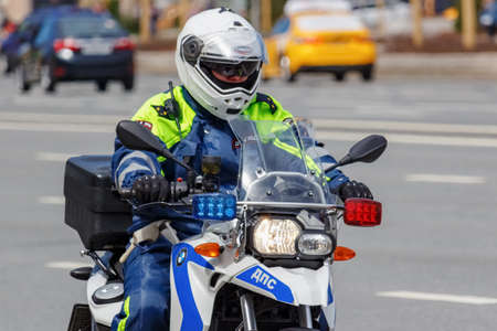 Moscow, Russia - May 04, 2019: Police on modern BMW motorcycle with flashing red and blue lights ride the street in sunny day Редакционное