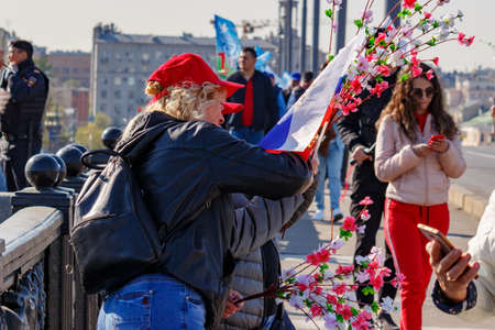 Moscow, Russia - May 01, 2019: Womans with flag and flowers go to the May Day demonstration on Red Square. May Day celebration in Moscow Editöryel