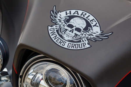 Moscow, Russia - May 04, 2019: Emblem of Harley Owners Group with skull and wings on matte black windproof shield of Harley Davidson motorcycle. Moto festival MosMotoFest 2019 Editorial