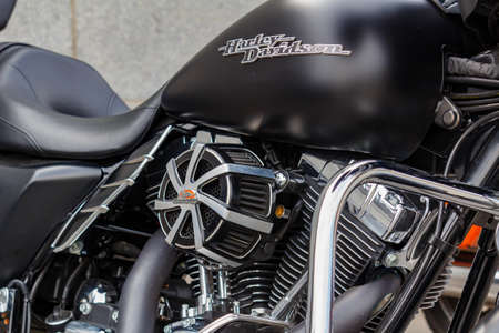 Moscow, Russia - May 04, 2019: Matte black fuel tank with Harley Davidson motorcycles emblem and chrome engine closeup. Moto festival MosMotoFest 2019