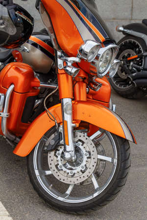 Moscow, Russia - May 04, 2019: Bright orange Harley Davidson motorcycle in a parking at sunny day. Moto festival MosMotoFest 2019