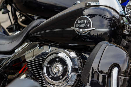 Moscow, Russia - May 04, 2019: Glossy black fuel tank with Harley Davidson motorcycles emblem and chromed engine closeup. Moto festival MosMotoFest 2019