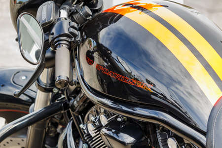 Moscow, Russia - May 04, 2019: Black fuel tank of Harley Davidson motorcycle with emblem and two yellow strip closeup. Moto festival MosMotoFest 2019