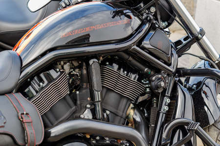 Moscow, Russia - May 04, 2019: Black engine and fuel tank with emblem of Harley Davidson motorcycles closeup. Moto festival MosMotoFest 2019