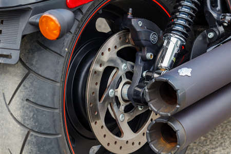 Moscow, Russia - May 04, 2019: Rear wheel and exhaust system pipes of Harley Davidson motorcycle closeup. Moto festival MosMotoFest 2019