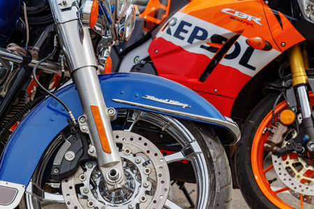 Moscow, Russia - May 04, 2019: Front wheel of Harley Davidson motorcycle closeup on a background of sport bike. Moto festival MosMotoFest 2019