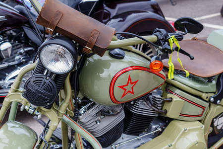 Moscow, Russia - May 04, 2019: Glossy khaki painted Harley Davidson motorcycle with soviet red star on fuel tank closeup. Moto festival MosMotoFest 2019 Editorial