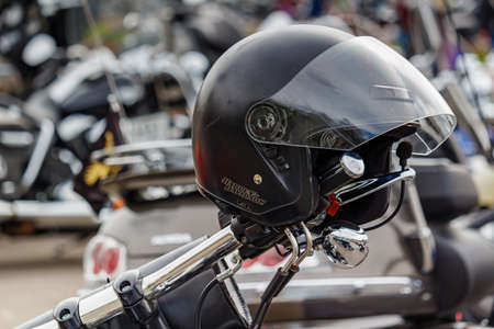 Moscow, Russia - May 04, 2019: Motorcycle helmet with Harley Davidson motorcycles emblem closeup on the handlebar. Moto festival MosMotoFest 2019