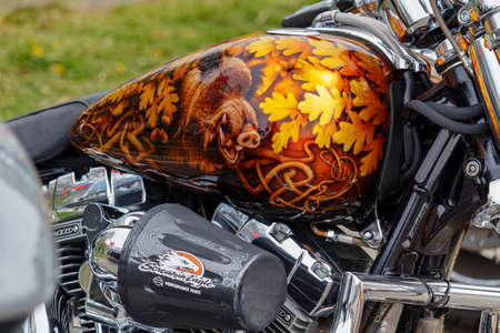 Moscow, Russia - May 04, 2019: Harley Davidson motorcycle with airbrushing of wild boar in oak leaves on fuel tank closeup. Moto festival MosMotoFest 2019