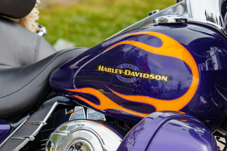 Moscow, Russia - May 04, 2019: Glossy blue fuel tank with Harley Davidson motorcycles emblem and orange flames closeup. Moto festival MosMotoFest 2019
