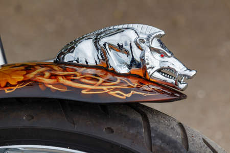 Moscow, Russia - May 04, 2019: Chromed figurine of wild boar on front fender of Harley Davidson motorcycle closeup. Moto festival MosMotoFest 2019