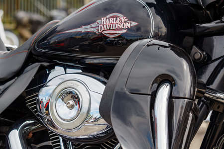 Moscow, Russia - May 04, 2019: Chrome engine and glossy black fuel tank with Harley Davidson motorcycles emblem closeup. Moto festival MosMotoFest 2019