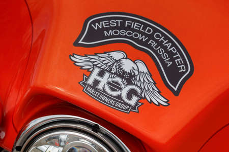 Moscow, Russia - May 04, 2019: Emblem of Harley Owners Group on bright orange windproof shield of Harley Davidson motorcycle. Moto festival MosMotoFest 2019