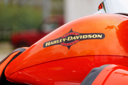 Moscow, Russia - May 04, 2019: Bright orange fuel tank with emblem of Harley Davidson motorcycles closeup. Moto festival MosMotoFest 2019
