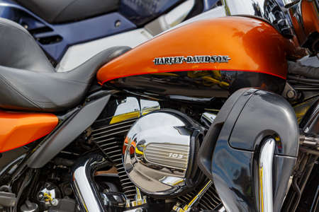 Moscow, Russia - May 04, 2019: Bright orange fuel tank with emblem of Harley Davidson motorcycles and chrome engine closeup. Moto festival MosMotoFest 2019