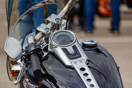 Moscow, Russia - May 04, 2019: Chromed speed indicator and ignition switch on the glossy black fuel tank of Harley Davidson motorcycle closeup. Moto festival MosMotoFest 2019 Editorial