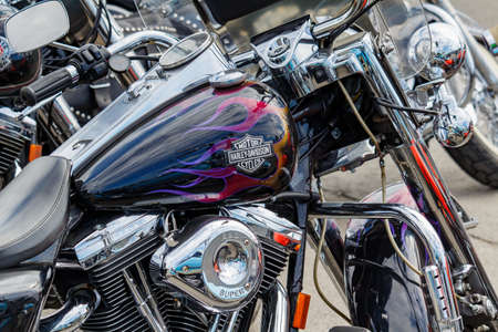 Moscow, Russia - May 04, 2019: Glossy black fuel tank with airbrushing and Harley Davidson motorcycle emblem closeup. Moto festival MosMotoFest 2019