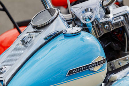Moscow, Russia - May 04, 2019: Glossy blue fuel tank with chromed speedometer and ignition switch of Harley Davidson motorcycle closeup. Moto festival MosMotoFest 2019
