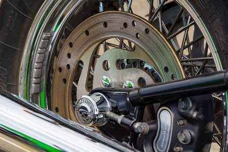 Moscow, Russia - May 04, 2019: Rear wheel with disc brake system and exhaust system pipes of Harley Davidson motorcycle closeup. Moto festival MosMotoFest 2019