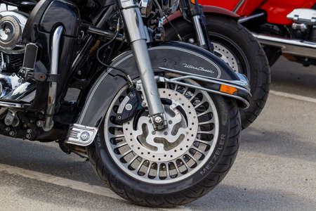 Moscow, Russia - May 04, 2019: Front wheel with black front fender of Harley Davidson motorcycle closeup. Moto festival MosMotoFest 2019