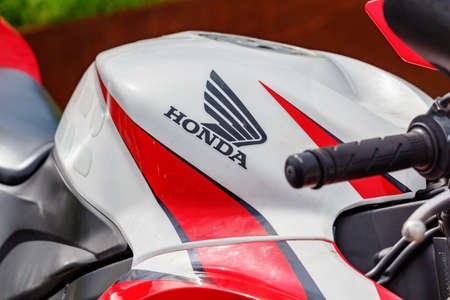 Moscow, Russia - May 04, 2019: Glossy red and white fuel tank of sports motorcycle with Honda emblem closeup. Moto festival MosMotoFest 2019 Editorial