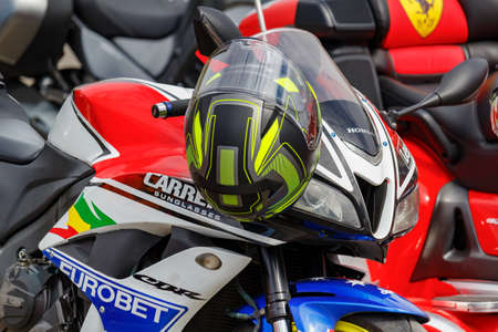 Moscow, Russia - May 04, 2019: Colored helmet on the handlebar of Honda sports motorcycle closeup. Moto festival MosMotoFest 2019