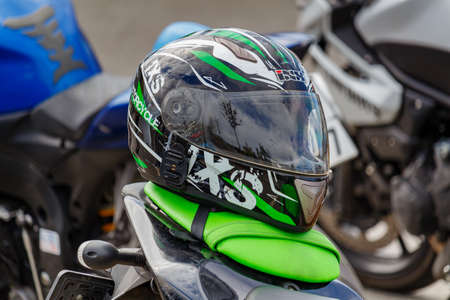 Moscow, Russia - May 04, 2019: Black sports motorcycle helmet IXS with green stripes and closed visor lies on a green leather seat of motorcycle closeup. Moto festival MosMotoFest 2019 Editorial