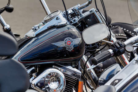 Moscow, Russia - May 04, 2019: Glossy black fuel tank of Harley Davidson motorcycle with emblem and chrome engine closeup. Moto festival MosMotoFest 2019