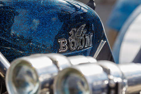 Moscow, Russia - May 04, 2019: Glossy blue fuel tank with emblem of BOOM tourist trike closeup against chromed headlights. Moto festival MosMotoFest 2019