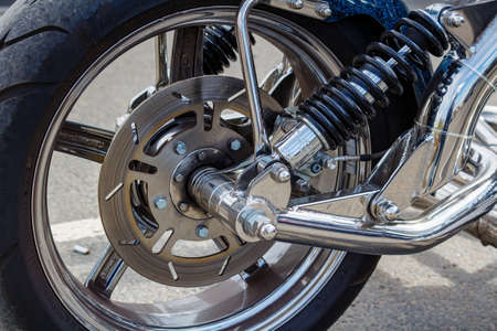 Moscow, Russia - May 04, 2019: Chromed front wheel with disc brake system and shock absorbers of BOOM tourist trike closeup. Moto festival MosMotoFest 2019 Editorial