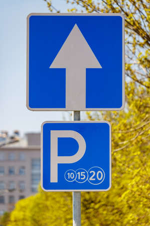 Road sign Paid parking closeup on the city street against green trees and blue sky in sunny day