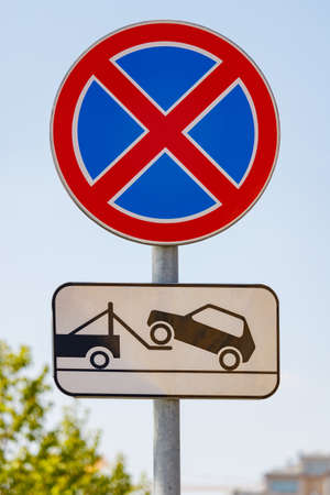 Road sign prohibiting the stopping of the car with a tow truck signboard against blue sky in sunny day closeup