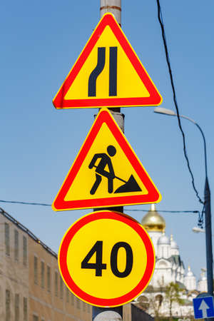 Road signs Road repairs and Speed limit 40 closeup against blue sky on the city street