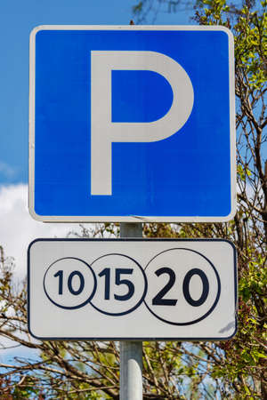 Road sign Paid parking against green trees and blue sky in sunny day closeup Foto de archivo