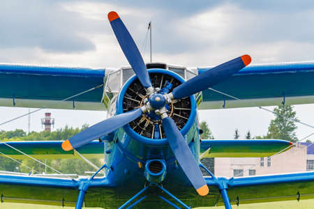 Blue painted legendary soviet aircraft biplane Antonov AN-2 closeup parked on the airfield against cloudy sky