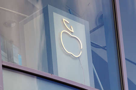 Moscow, Russia - June 02, 2019: Glowing Apple company logo behind the window glass of office building
