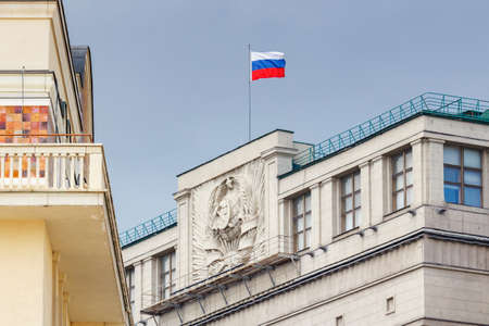 Moscow, Russia - June 02, 2019: Waving flag of Russian Federation on the roof of building of State Duma of Russian Federation in Moscow against blue sky