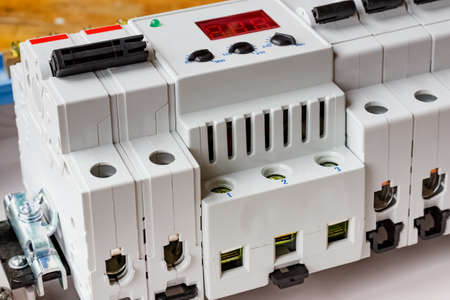Automatic circuit breakers and voltage limiter installed on DIN rail in the white plastic mounting box closeup Фото со стока