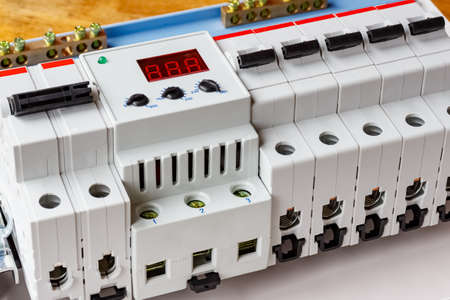 Installed automatic circuit breakers with voltage limiter in the white plastic mounting box closeup