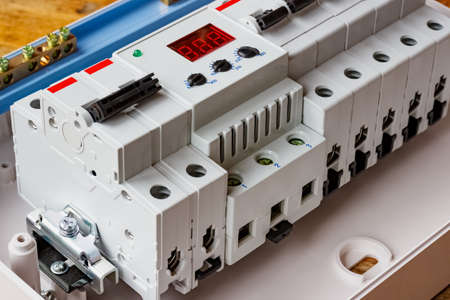 White plastic mounting box with installed automatic circuit breakers and voltage limiter closeup Фото со стока